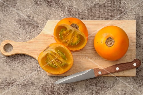 Fresh naranjillas on a chopping board with a knife