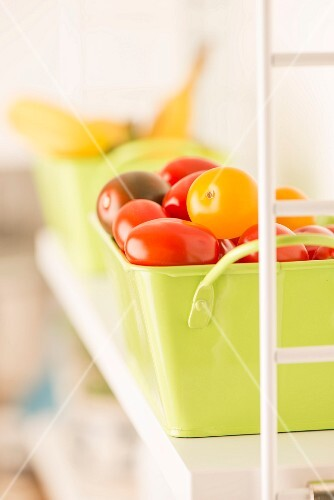 A green metal box full of assorted tomatoes on the kitchen shelf