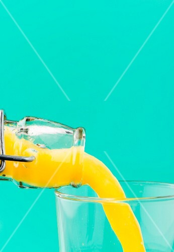 Orange juice with bits of pulp being poured from a bottle into a glass
