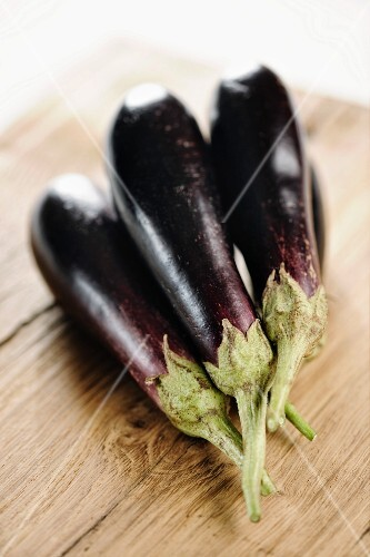 Several aubergines on a wooden board