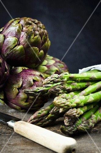 Purple artichokes and stalks of green asparagus on a wooden board