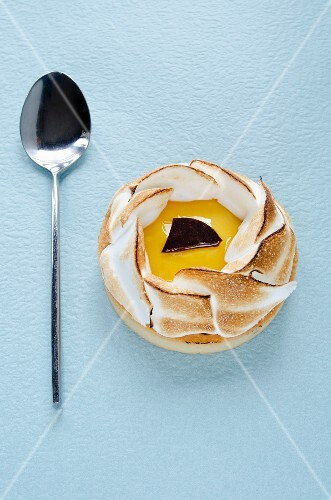 An individual lemon meringue tart and a spoon on a blue surface