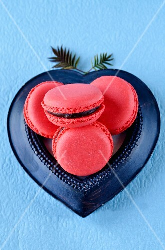 Raspberry macaroons with chocolate filling in a heart-shaped dish on a blue surface
