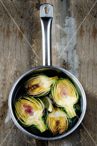Halved purple artichokes in a saucepan of water on a rustic wooden surface