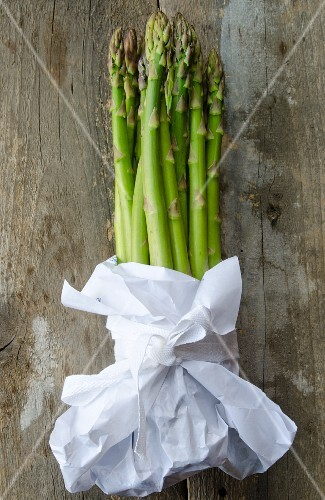Stalks of green asparagus wrapped in white paper on a wooden surface