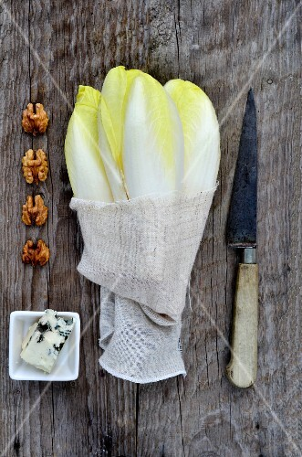Ingredients for salad: chicory, Roquefort and walnuts on a wooden surface