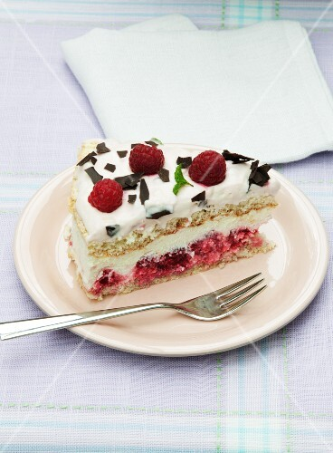 A slice of cream cheese layer cake with raspberries