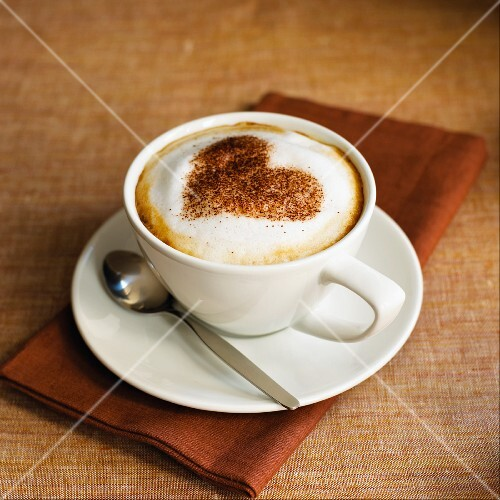 A cup of Cappuccino with heart shape from cocoa powder