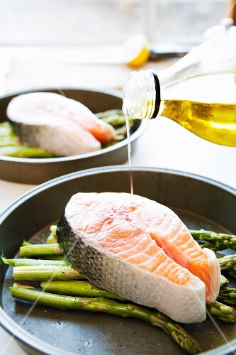 Drizzling olive oil on a salmon steak and asparagus