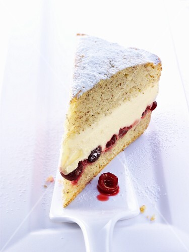 A slice of cream cheese layer cake with cherries