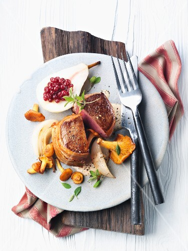 Medallion of venison with chanterelles and a pear stuffed with cranberries