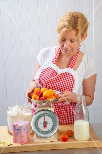 A woman weighing apricots