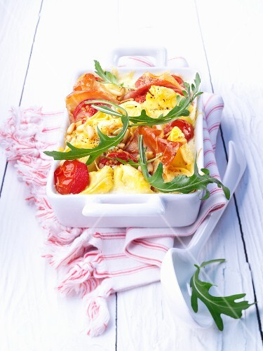 Tortellini casserole with bacon, tomatoes and rocket
