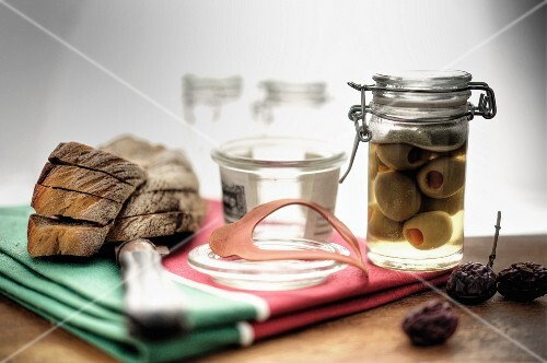 Pickled olives in a pickling jar with locking lid, sliced Farmer's bread next it