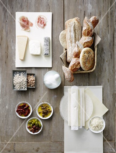 Still life with bread, cheese, raw ham, olives, capers, dried tomatoes and rice paper