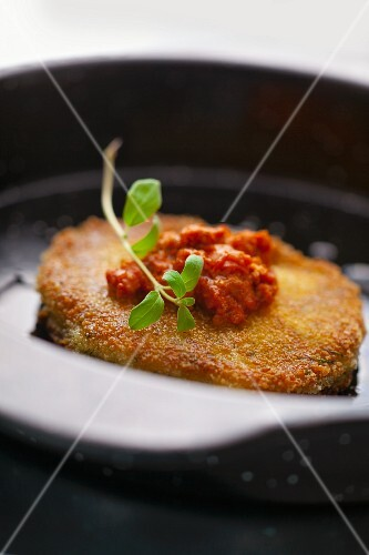 Breaded pork chop with tomato sauce and oregano