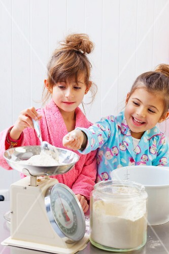 Two girls weighing flour on kitchen scales