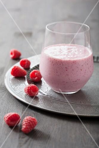 A raspberry milkshake and fresh raspberries