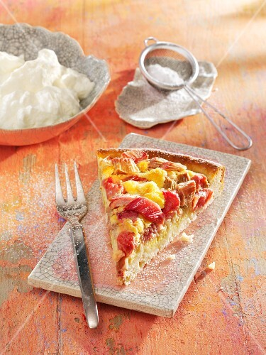 A slice of rhubarb and coconut tart with cream