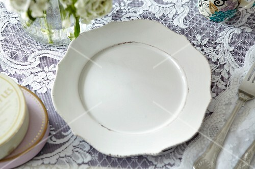 A white plate on a lace cloth