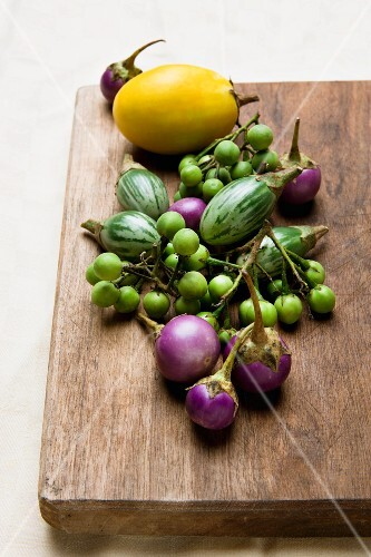 Assorted types of mini aubergine on a wooden board