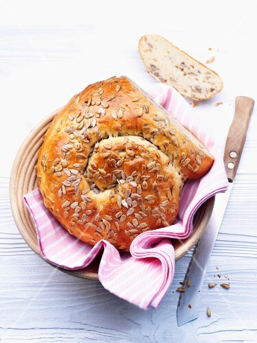 A bread basket holding a loaf of bread made with quark and oil and topped with sunflower seeds