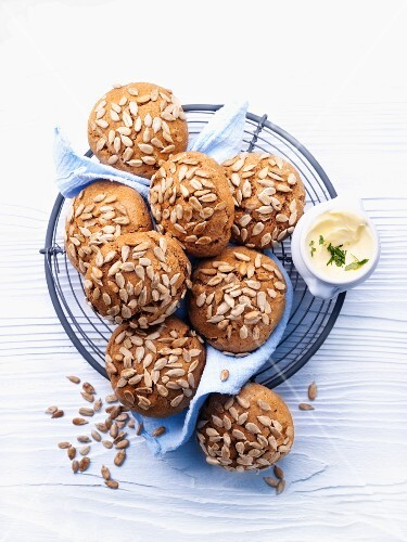 Sunflower seed rolls and butter in a bread basket