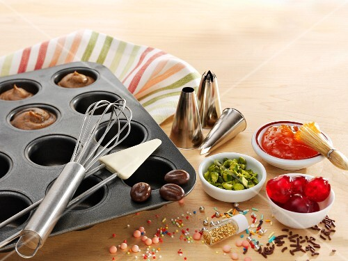 A muffin tray with batter, baking utensils and toppings