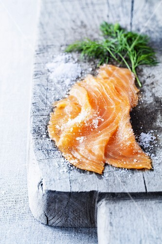 Smoked salmon with dill and coarse sea salt on a rustic wooden board
