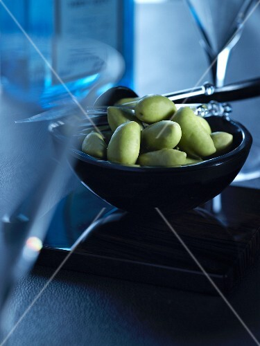 A bowl of green olives between martini glasses