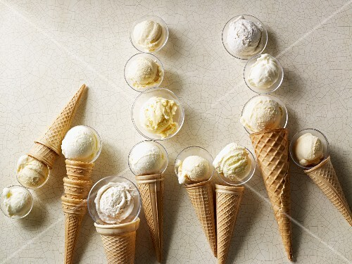 Scoops of vanilla ice cream in wafer cones and glass dishes
