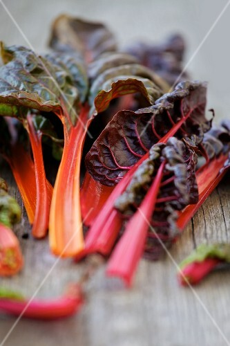 Red chard leaves on a wooden surface