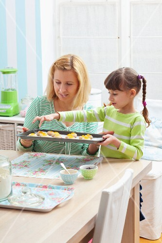 A mother and daughter holding a baking tray of unbaked jam biscuits