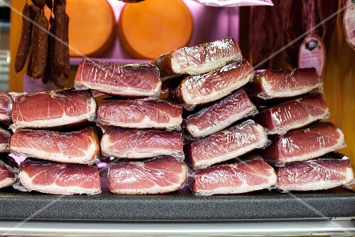 A stack of packaged dry-cured ham at the market
