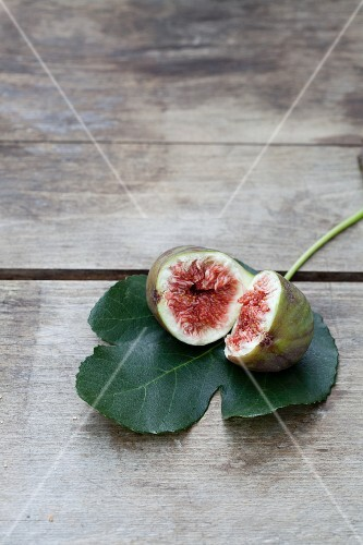 A halved fig on a fig leaf