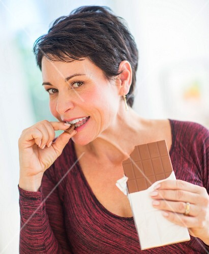 A woman nibbling on a piece of chocolate