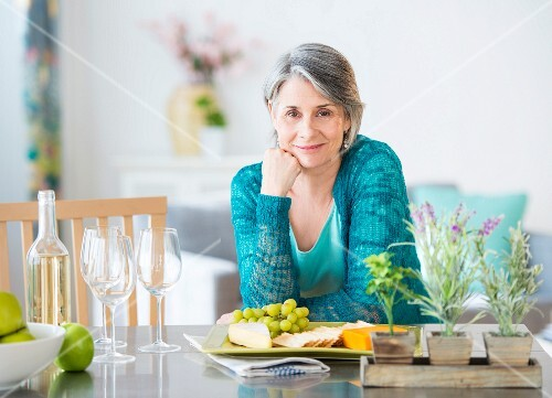 A woman leaning on a kitchen table
