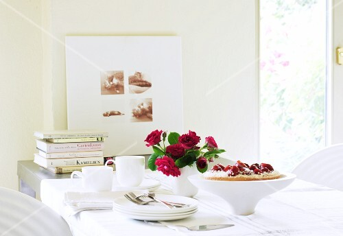 A table laid with strawberry cake, a bunch of roses, a coffee service and books