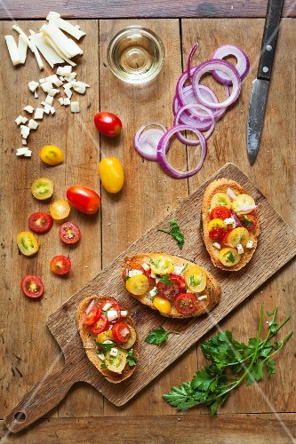 Red and yellow grape tomato bruschetta with red onions and mozzarella