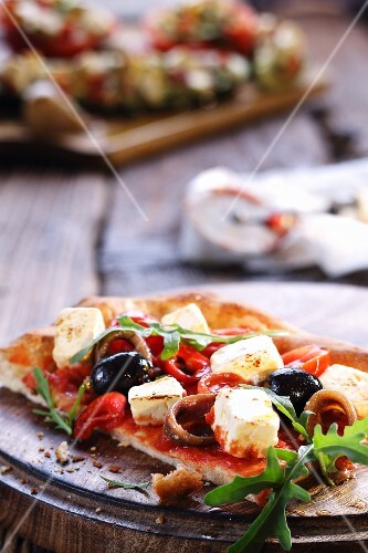 Slice of pizza with olives, feta and anchovies