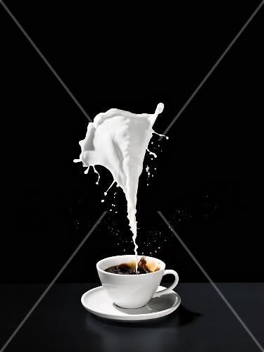 A splash of milk above a cup of coffee