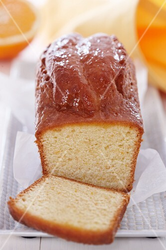Orange cake, cooked in a loaf tin, partly sliced