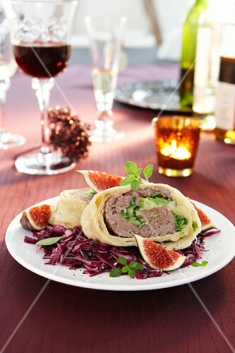 Pasta roulade filled with minced meat, on a red cabbage salad with figs