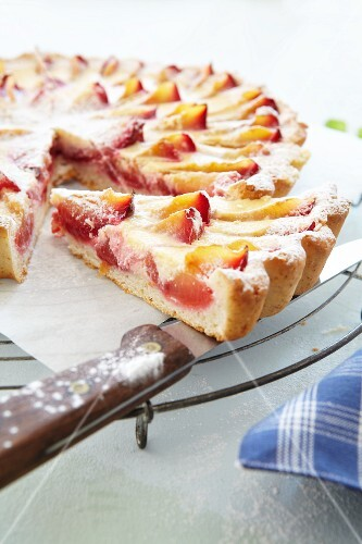Plum tart, partly sliced, on a cooling rack