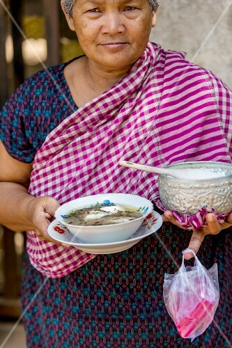 A woman serving soup with rice (Cambodia)