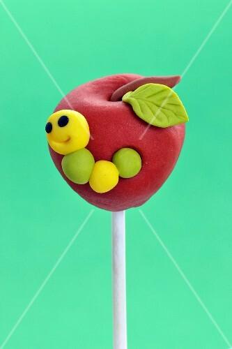 A cake pop designed to look like an apple