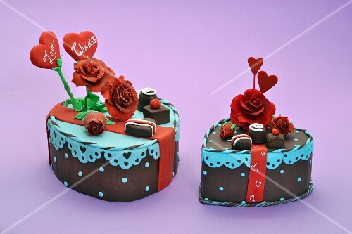 Two heart-shaped cakes decorated with roses and sweets