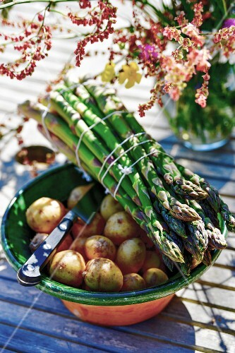 A bunch of asparagus on top of a bowl of potatoes