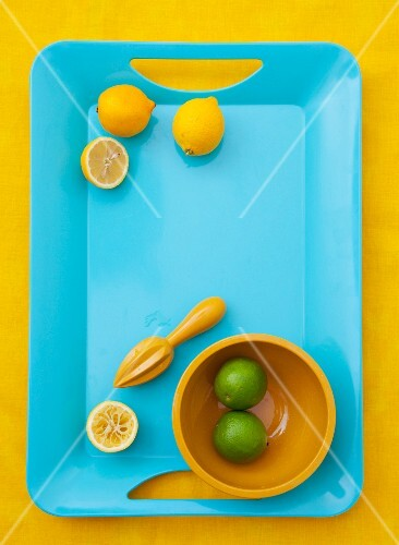 Lemons, whole and halved, with a lemon squeezer; limes in a bowl