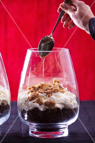 A woman drizzling honey onto a layered dessert of chocolate cake, cream and oat biscuits